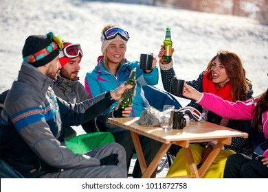 Group of happy friends cheering with beer after skiing day in cafe at ski resort