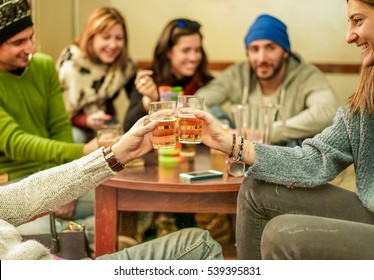 Group of happy friends cheering with beer after skiing day in bar pub restaurant - Young people toasting aperitif and playing board games - Concept about good and positive mood - Focus on cheers hands