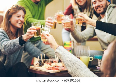 Group of happy friends cheering with beer after skiing day in bar pub restaurant - Young people toasting appetizer in brewery chalet - Concept about good and positive mood - Focus on right bottom hand