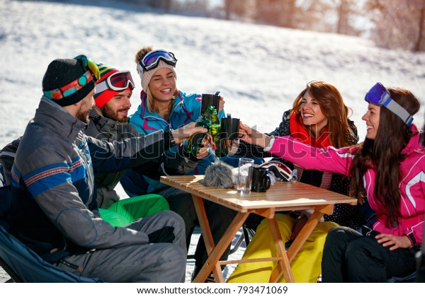 Group of happy friends cheering with drink after skiing day in cafe at ski resort