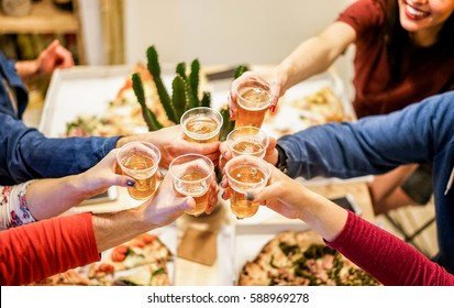 Group of happy friends cheering at home with beer - Young people having fun together eating italian pizza take away - Dinner,party and friendship concept - Focus on glasses