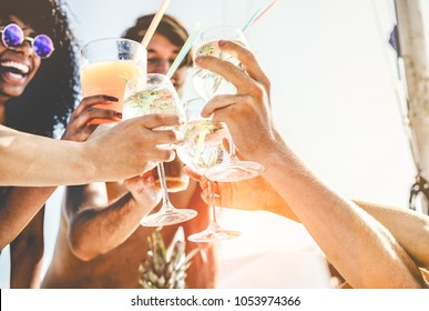 Group of happy friends cheering with tropical cocktails at boat party - Young people having fun in caribbean sea tour - Youth and summer vacation concept - Focus on bottom hands glass
