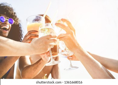 Group of happy friends cheering with tropical cocktails at boat party - Young people having fun in caribbean sea tour - Youth and summer vacation concept - Focus on close-up hands glass