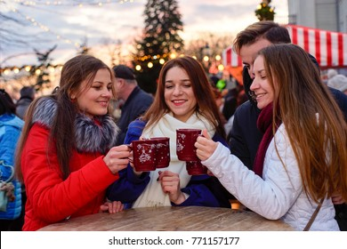 Group of happy friends clinking mugs with hot red mulled wine at Christmas market