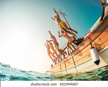 Group of happy friends diving from sailing boat into the sea - Young people jumping inside ocean in summer vacation - Main focus on right man - Travel and fun concept - Fisheye lens distortion
