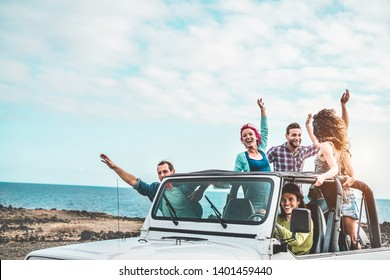 Group of happy friends doing excursion on desert in convertible 4x4 car - Young people having fun traveling together - Friendship, tour, youth lifestyle and vacation concept - Focus on right guys