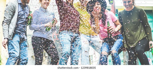 Group of happy friends doing party throwing confetti and drinking beer - Young millennials people having fun celebrating together - Youth, friendship and trendy lifestyle - Focus on bottles hands