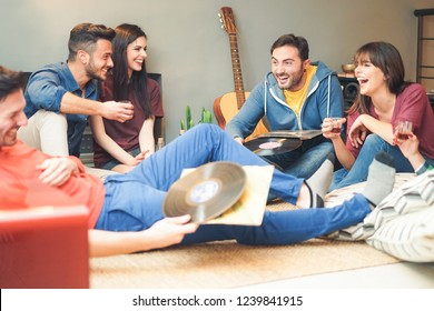 Group of happy friends doing party listening vintage vinyl disc at home - Young people having fun drinking shots and laughing together in their apartment - Friendship, music, youth lifestyle holidays