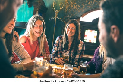 Group of happy friends drinking beer at brewery bar restaurant - Friendship concept with young millenial people enjoying time together having fun vintage pub - Focus right woman - High iso image