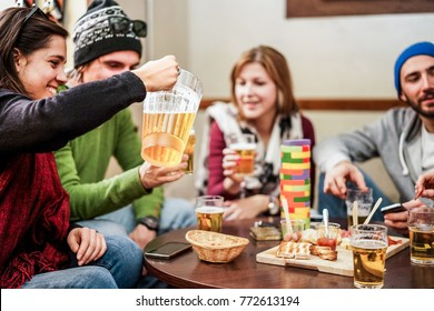 Group of happy friends drinking with beer after skiing day in bar pub restaurant - Young people cheering in brewery chalet party - Friendship and holidays concept - Focus on left woman hand and jug