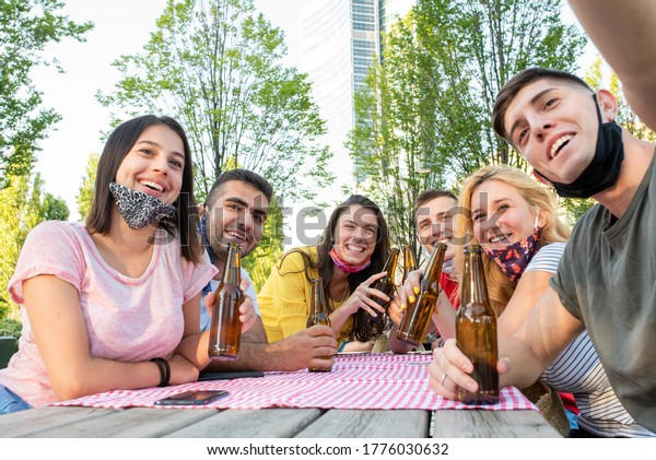 Group of happy friends drinking beers, adult people toasting together outdoors and wearing protective masks, focus on faces in the background - Summer lifestyle,  prevention of coronavirus, new normal