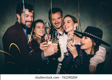 Group of happy friends drinking champagne and celebrating New Year. New year party. Birthday party