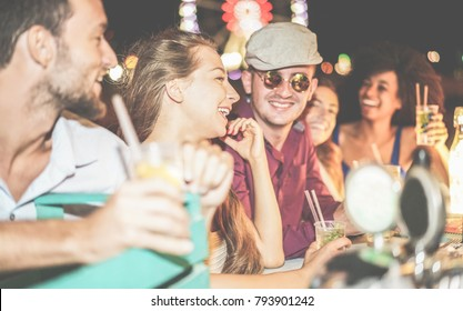 Group of happy friends drinking cocktails and laughing at beach party outdoor - Young tourist having fun in summer vacation - Focus on left girl eye - Nightlife, holidays and youth concept