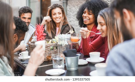 Group of happy friends drinking coffee and cappuccino at vintage bar outdoor - Young millennials people doing breakfast together - Friendship, youth and food concept - Focus on afro girl face
