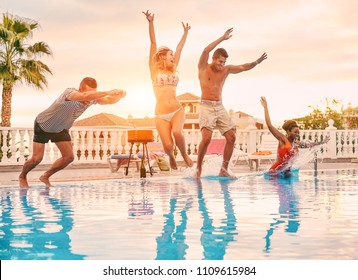 Group of happy friends drinking jumping in pool sunset party - Young diverse culture people having fun in tropical vacation - Holiday, youth and friendship concept - Main focus on center guys
