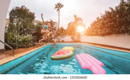 Group of happy friends drinking jumping in pool at sunset party - Young diverse culture people having fun in tropical vacation - Holiday, youth and friendship concept - Main focus on close-up girl