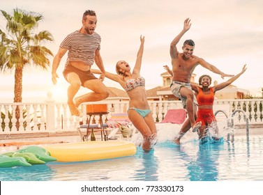 Group of happy friends drinking jumping in pool sunset party - Young diverse culture people having fun in tropical vacation - Holiday, youth and friendship concept - Main focus on right man face