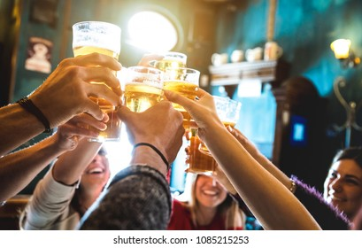 Photo of Group of happy friends drinking and toasting beer at brewery bar restaurant - Friendship concept with young people having fun together at cool vintage pub - Focus on middle pint glass - High iso image