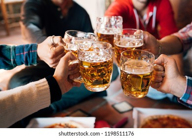 Group of happy friends drinking and toasting beer at brewery bar restaurant - Friendship concept with young people having fun together at cool vintage pub - Focus on middle pint glass