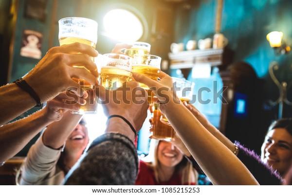 Gruppe glücklicher Freunde, die Bier trinken und toasten im Brauereibar-Restaurant - Freundschaftskonzept mit jungen Leuten, die sich in einem coolen Vintage-Pub amüsieren - Fokus auf Mittelpint Glas - High-ISO-Image