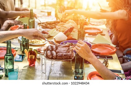Group of happy friends eating and drinking beers at barbecue dinner on sunset time - Adult people having meal together outdoor - Focus on fork sausages - Summer lifestyle, food and friendship concept