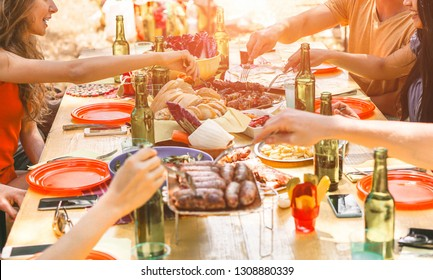 Group of happy friends eating and drinking beers at barbecue dinner at sunset - Adult people having meal together outdoor - Focus on top hands - Summer lifestyle, food and friendship concept