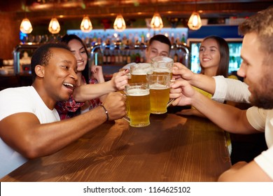 Group of happy friends enjoying beer at design pub, toasting and laughing.
