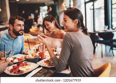 Grupo de amigos felizes tomando café da manhã no restaurante