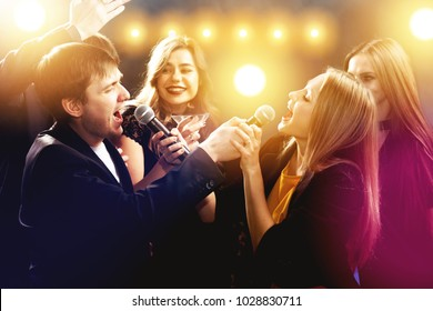Group of happy friends are having fun, singing and dancing in karaoke club