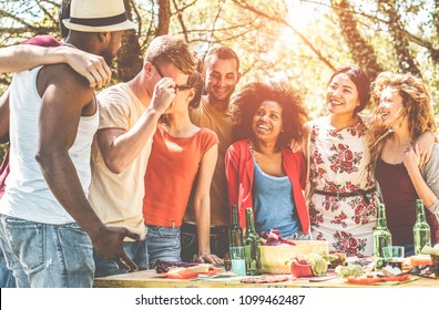 Group of happy friends having fun at barbecue party outdoor into the wood nature - Young people doing bbq dinner - Youth lifestyle, food and friendship concept - Main focus on afro girl face