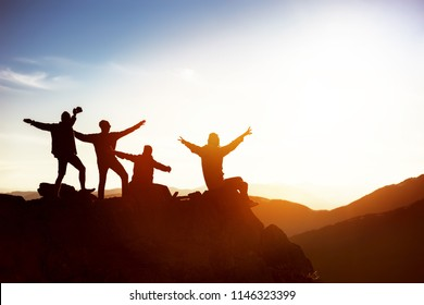 Group of happy friends having fun at sunset time on mountain top