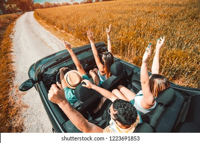 Group of happy friends having fun with hands up on a convertible car at roadtrip. Concept about transport, rental cars, people and lifestyle
