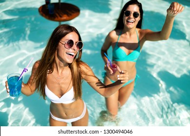 Group of happy friends having fun dancing at swimming pool outdoors