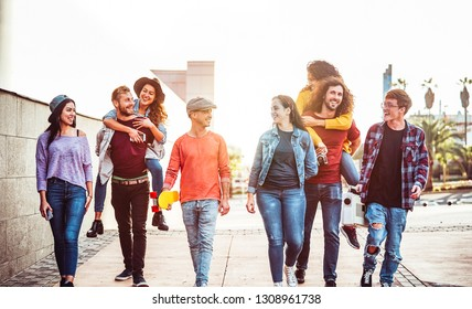 Group of happy friends having fun outdoor - Young people piggybacking while laughing and walking together in the city center - Friendship, millennial generation, teenager and youth lifestyle concept