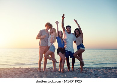 Group of happy friends having fun at ocean beach at dawn