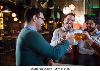 Group of happy friends having fun and drinking beer at pub