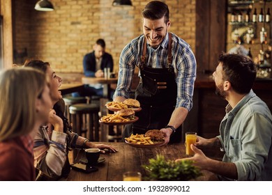 Group of happy friends having fun while waiter is serving them food in a pub. Focus is on waiter.