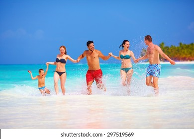 group of happy friends having fun together on tropical beach