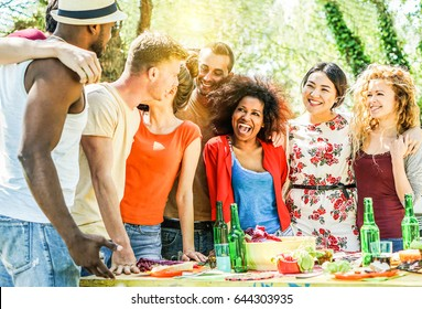 Group of happy friends having fun at barbecue party outdoor in house backyard - Young diverse culture people making bbq dinner - Youth, food and friendship concept - Focus on right guys - Warm filter