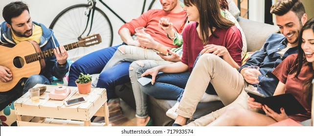 Group of happy friends having fun in hostel living room - Trendy young people enjoying time together playing music and watching videos with tablet - Youth concept -  Soft focus on center girl face