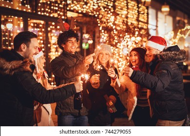 Group of happy friends having fun with sparklers on night Christmas party.
