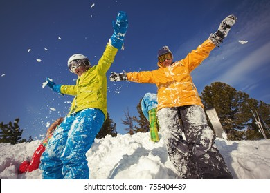 Group of happy friends having fun playing in snow. Ski and snowboard holiday