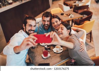 Group of Happy friends having making selfie in cafe