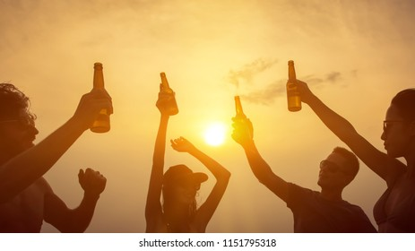 Group of happy friends having party celebrating and drinking at the beach on vacation in summer twilight sunset