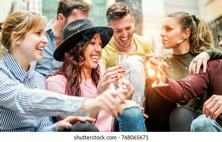 Group of happy friends having party with champagne,confetti and sparklers outdoor - Young students celebrating drinking and laughing - Friendshi and youth concept - Focus on center girl with hat