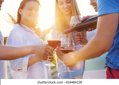 Group of happy friends having red wine on the beach. Sunset beach party