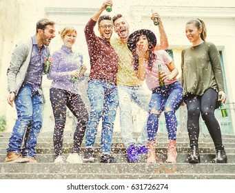Group of happy friends having a street party drinking beers while confetti are falling down - Hilarious young people celebrating a birthday outdoor - Friendship concept