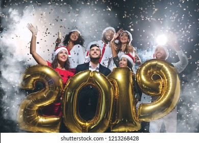 Group of happy friends holding golden balloons in form of 2019 at New Year's Eve party, confetti and smoke background, copy space