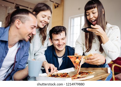 Group of happy friends at home party. Eating pizza together. Asian woman taking picture of the the slice to share memory