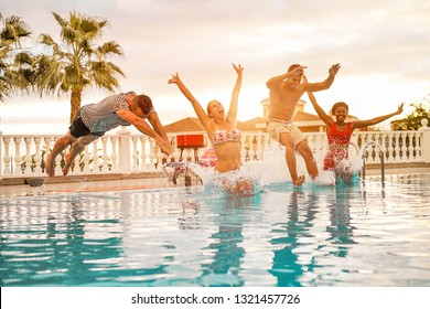 Group of happy friends jumping inside swimming pool - Young crazy people having fun in tropical vacation - Holiday, youth, summer lifestyle and friendship concept - Focus on faces